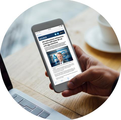 Photo of person holding mobile phone display The Insurer website